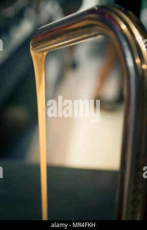White chocolate flowing from a faucet metal. - Stock Photo