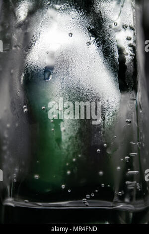 Texture water drops on glass of water that look like ice block. Green bottle appears blurred in the background - Stock Photo