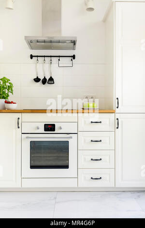 White cabinet in minimal kitchen interior with wooden countertop. Real photo - Stock Photo