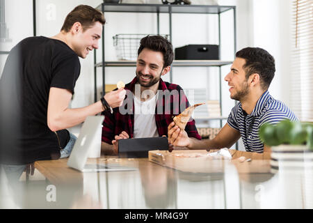 Smiling friends eating pizza and talking about digital cryptocurrency - Stock Photo