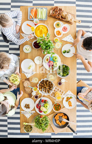 Top view on table with food. Group of kids eating healthy dinner with vegetables - Stock Photo