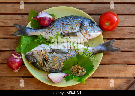 Two raw Sea breams in a plate, soused by salt, olive oil and dry rosemary, ready for grilling, view from above - Stock Photo
