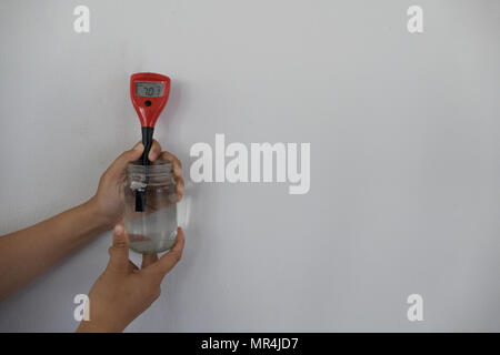 hand measureing pH in soil solution. research & science concept - Stock Photo