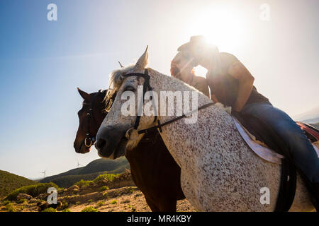 love scene between young beautiful coule riding two nice horses in the nature. windmill for green energy and better future on the background. alternat - Stock Photo