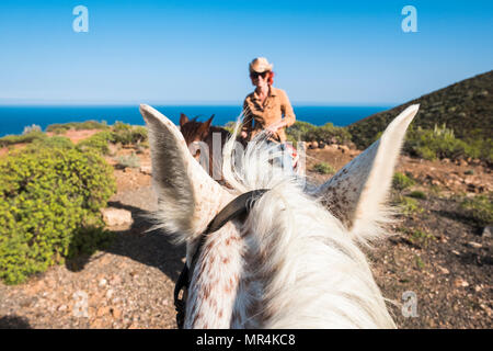 nice rare portrait of a beautiful girl ride a horse made by another rider on a white horse. funny and savage picture for a couple in contact with the  - Stock Photo