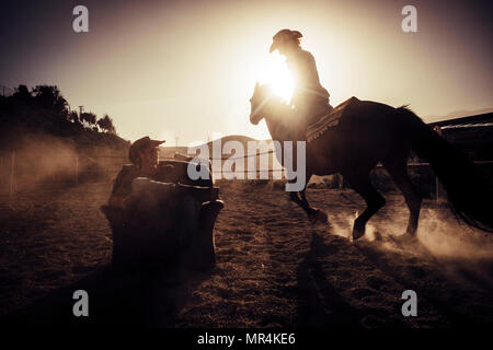 hero concept dramatic and advertising style image for cowgirl making dust riding a horse near a cowboy sit down on a chair in the middle of the track. Stock Photo