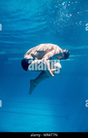 underwater picture of male swimmer in cap and goggles - Stock Photo