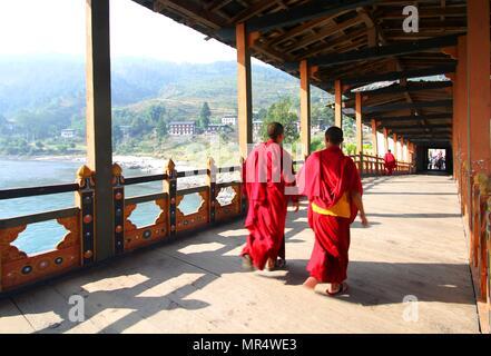 Two young monks walking on  PUNA MOCCHU BAZAM : Antique  wooden bridge at Punakha Dzong Monastery or Pungthang Dewachen Phodrang  Bhutan - Stock Photo