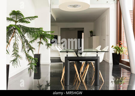 Open dining room in white with modern glass table - Stock Photo