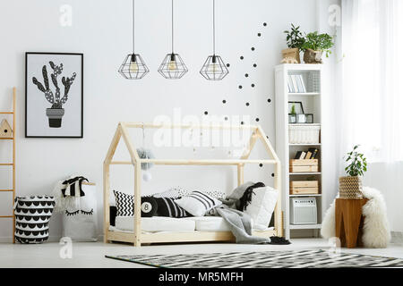 Modern baby bedroom in white with bed, bookcase, and carpet - Stock Photo