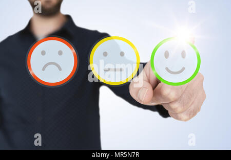 man in blue shirt touching translucent interface with rating smiley buttons,  customer feedback concept - Stock Photo