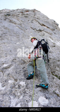 mountain guide at the start of a steep climbing route in the Swiss Alps - Stock Photo