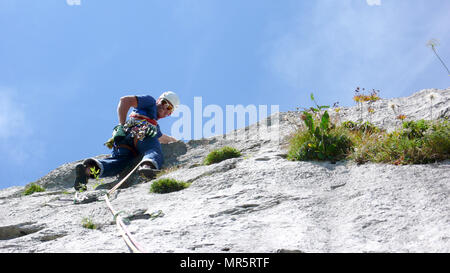 mountain guide climbing a steep slab pitch of a hard rock climbing route in the Alps of Switzerland - Stock Photo