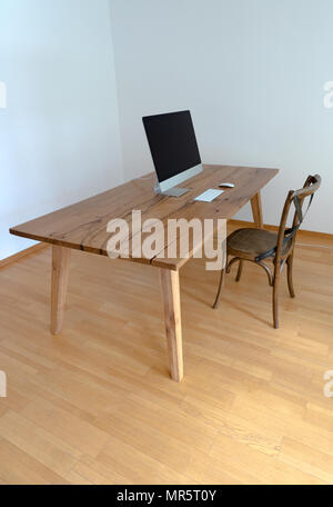 minimalist office with table and chair and computer - Stock Photo
