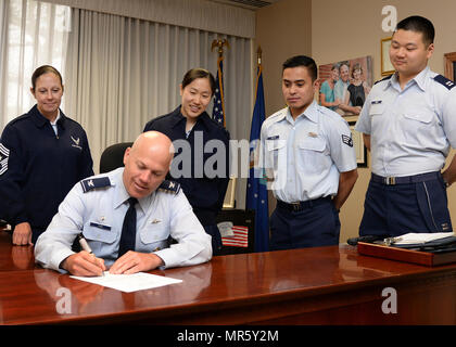 Col. Roman L. Hund, installation commander, signs a proclamation establishing May as Asian American Pacific Islander Heritage Month at Hanscom Air Force Base, Mass., May 1, while Command Chief Master Sgt. Patricia L. Hickey, left, 1st Lt. Yeoju Kim, Senior Airman Martin Jerome Castro and Capt. Kenneth Suen look on. The proclamation calls upon all military, civilian and family members at Hanscom to mark the monthlong observance by participating in base wide activities, sponsored by the Asian Pacific American Heritage committee. (U.S. Air Force photo Linda LaBonte Britt) - Stock Photo