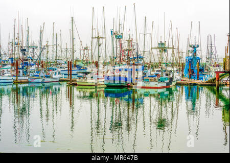 Newport, Oregon,USA - August 23, 2016:  Slowly lifting fog above commercial fishing boats in New Port Harbor on the Oregon Coast - Stock Photo
