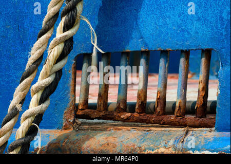 Closeup of a rusted section of a hull of a boat that is tied by a rope to the dock in Newport Harbor on the Oregon Coast. - Stock Photo
