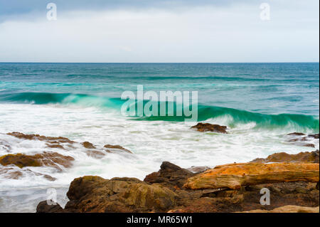 Waves roll in to a rocky beach littered with driftwood in Yachats, on the Oregon Coast - Stock Photo