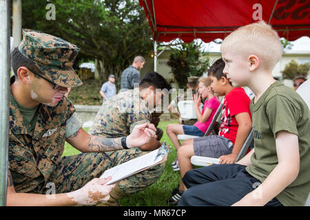 U.S. Navy Petty Officer 3rd Class Joseph Irons, a Hospital Corpsman with Headquarters Battalion, 3rd Marine Division, conducts a check up on a Marine Corps service member's son aboard Camp Courtney, Okinawa, Japan, May 20, 2017. 3rd Marine Division hosted a Kids Warrior Day to help bring the families of Marines and Sailors closer together and give them the opportunity to see what their Marine or Sailor is doing throughout the Division. (U.S. Marine Corps photo by Lance Cpl. Jordan A. Talley) - Stock Photo