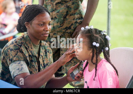 U.S. Marine Corps Cpl. Molly Karani, a motor transportation mechanic with Truck Co, Headquarters Battalion, 3rd Marine Division, paints the face of a Marine Corps service member's daughter aboard Camp Courtney, Okinawa, Japan, May 20, 2017. 3rd Marine Division hosted a Kids Warrior Day to help bring the families of Marines and Sailors closer together and give them the opportunity to see what their Marine or Sailor is doing throughout the Division. (U.S. Marine Corps photo by Lance Cpl. Jordan A. Talley) - Stock Photo