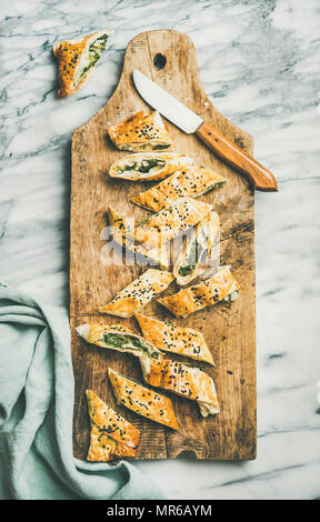 Flat-lay of fresh Turkish borek roll cut in slices slices with spinach, feta cheese, black cumin seeds on wooden board over grey marble background, to - Stock Photo
