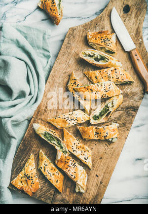 Flat-lay of fresh Turkish borek roll with spinach, feta cheese, black cumin seeds cut in slices on rustic wooden board over grey marble background, to - Stock Photo