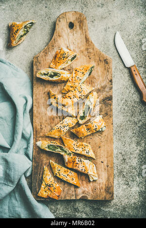 Flat-lay of fresh Turkish borek roll with spinach, feta cheese, black cumin seeds cut in slices on wooden board over concrete background, top view. Tr - Stock Photo