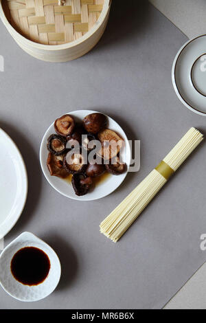 Still life in asian style with soaked siitake mushrooms in white bowl - Stock Photo