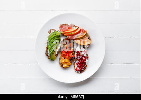 Variety of bruschettas with avecado, prosciutto, tomatoes and pomegranate seeds on white plate - Stock Photo