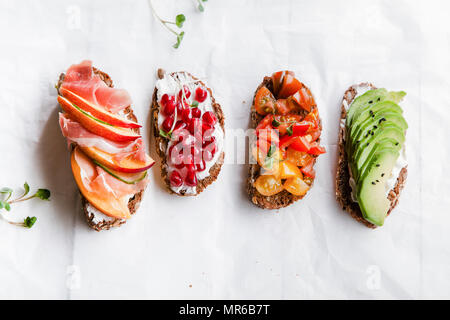 Variety of bruschettas with avecado, prosciutto, tomatoes and pomegranate seeds on white background - Stock Photo