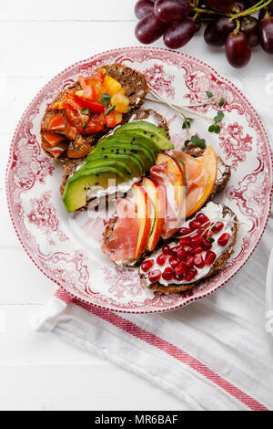 Variety of bruschettas with avecado, prosciutto, tomatoes and pomegranate seeds on vintage porcelain plate - Stock Photo