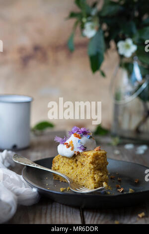 Carrot cake with cream and wild flowers - Stock Photo