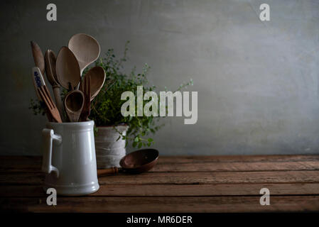Rustic still life of a kitchen counter with worn wooden utensils in a porcelain pitcher and a lovely tangled oregano plant in the background. - Stock Photo