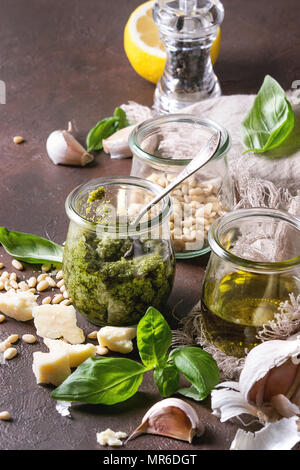 Traditional Basil pesto sauce in glass jar with ingredients above fresh basil, olive oil, parmesan cheese, garlic, pine nuts, lemon on cloth over dark - Stock Photo
