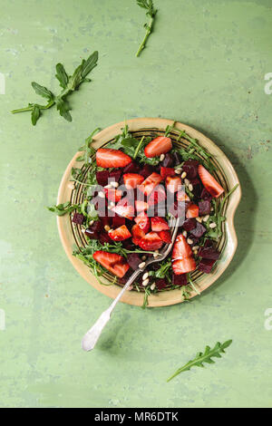 Beetroot and strawberry salad served with arugula and nuts on ceramic plate with fork over green texture background. Top view, space. Healthy eating - Stock Photo