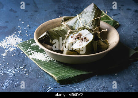 Asian rice piramidal steamed dumplings from rice tapioca flour with meat filling in banana leaves served in ceramic bowlwith rice above over blue text - Stock Photo