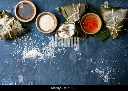 Asian rice piramidal steamed dumplings from rice tapioca flour with meat filling in banana leaves. Ingredients and sauces above over blue texture back - Stock Photo