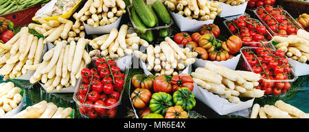Market stall with fresh spring season vegetables at Parisian street farmers market. White asparagus, tomatoes, cucumbers. - Stock Photo