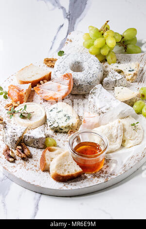 Cheese plate assortment of french cheese served with honey, walnuts, bread and grapes on white wooden serving board over white marble texture backgrou - Stock Photo