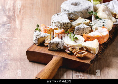 Cheese plate assortment of french cheese served with honey, walnuts, bread and grapes on rustic wooden serving board over wood texture background. Clo - Stock Photo