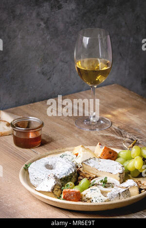 Cheese plate assortment of french cheese served with honey, walnuts, bread and grapes on ceramic plate and glass of white wine over wooden table with  - Stock Photo