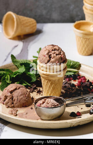 Homemade chocolate raspberry ice cream in small waffle cup served with frozen berries, fresh mint, chopped dark chocolate and metal spoon in ceramic p - Stock Photo