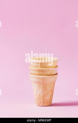 Stack of empty waffle cups for ice cream over pink pastel pin-up background. Copy space. - Stock Photo