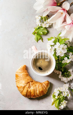 Pink mug of black espresso coffee, french croissant, cream and spring flowers magnolia, blooming cherry branches over grey texture background. Top vie - Stock Photo