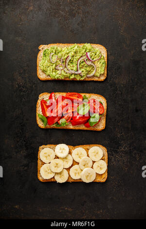Different kinds of colorful whole grain bread sandwiches on dark background from above (top view). Clean eating, healthy, diet, weight loss food conce - Stock Photo