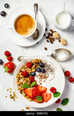 Healthy breakfast with coffee and Bowl of homemade granola with yogurt and fresh berries on white marble background. Top view, flat lay - Stock Photo