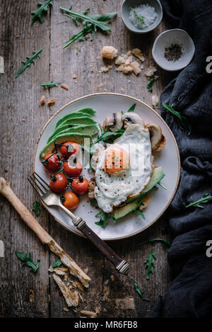 Egg and sliced avocado on toast, set on a rustic kitchen table - Stock Photo
