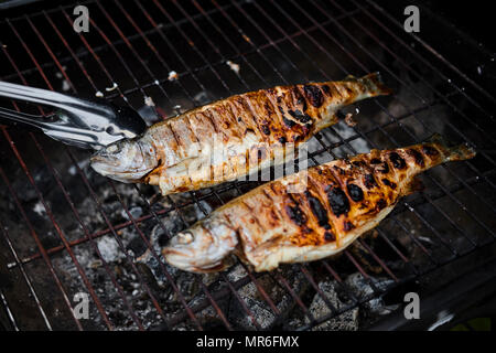 Top down view of man grilling fish and shrimps on skewers on barbecue with a tray of raw vegetables on the side - Stock Photo