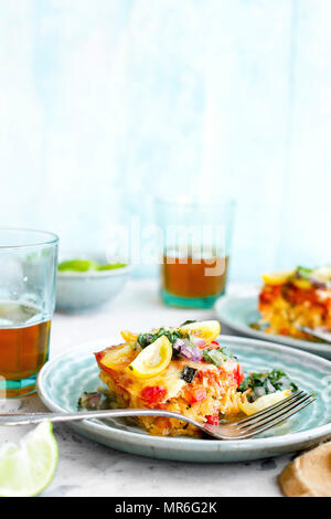 Spaghetti Squash Enchilada Casserole served with Cilantro Salsa and Beer. Photographed on a light grey background. - Stock Photo