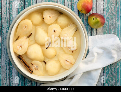 A bowl of poached pears halves and a cinnamon stick in syrup beside two red pears. - Stock Photo